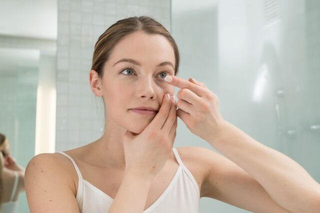 girl placing in contact lenses